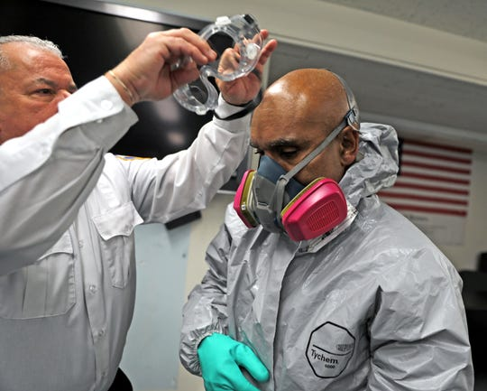 Lt. Raul Perez helps fellow New Rochelle Firefighter Marstus Hewitt put on special protective gear firefighters wear when responding to a potential Coronavirus call at New Rochelle fire headquarters in New Rochelle March 18, 2020.