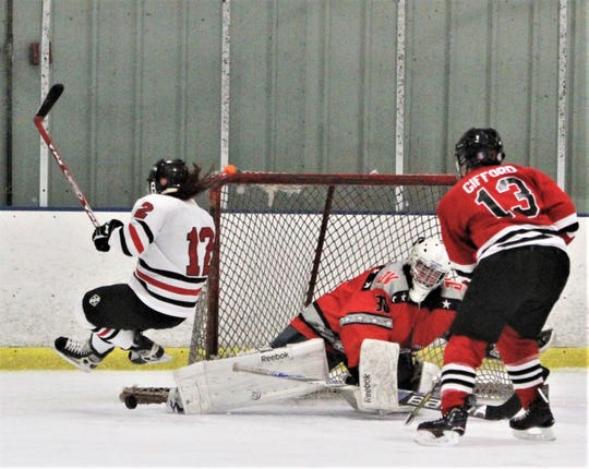 Westchester Wildcat goalie Cathy Lucido makes right-pad save on Quarry Cat Sarah Rozek (12) as she goes airborne Saturday during the Alisha Weissman Memorial Tournament at Brewster Ice Arena.