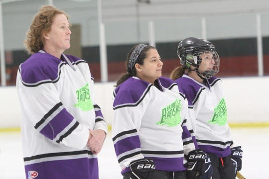 Brewster Banshees players (l-r) Sue Hughey Driscoll, Jennifer Neal and Trish Farren stand in silence for 88 seconds to honor late Danbury Battle Axe player Alisha Weissman Saturday, March 15, 2020 at Brewster Ice Arena.