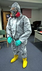 New Rochelle Firefighter Marstus Hewitt puts on special protective gear that firefighters wear when responding to a potential Coronavirus call at New Rochelle fire headquarters on March 18, 2020.