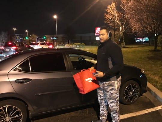 DoorDash driver Marco Valera grabs his delivery bag to pick up delivery food from Chic-Fil-A in Bear. He wanted to cash in on businesses only offering take out or delivery during the state of emergency.