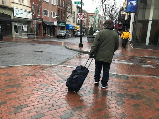 A homeless man who identified himself as Ricky lugs his belongings down Wilmington's Market Street. Ricky, who stays at the Sunday Breakfast Mission, was looking for somewhere to go during the daytime as coffee shops and libraries were off-limits during the coronavirus outbreak.