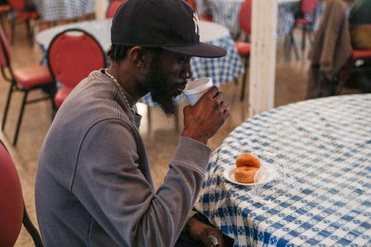 "Corey Moon sips coffee at a free breakfast at St. Patrick's, which remains open with precautions in place despite the threat of coronavirus. ""You just gotta hope that there are places you can go where people won't judge you,"" he said."