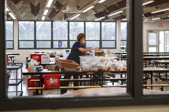 Gwen O'neal prepares bags stuffed with lunch and breakfast foods for kids in the Brandywine School District on Tuesday morning. She volunteered to work with a handful of others to ensure kids at home due to the coronavirus shutdown still have enough to eat.