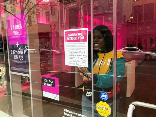 T-Mobile employee Emotti Zeigler puts up a sign announcing limited hours on Tuesday morning at the cell phone service store on downtown Wilmington's Market Street. Along the city's central business corridor, door after door in restaurants and cafes were adorned with signs announcing coronavirus-related restrictions.