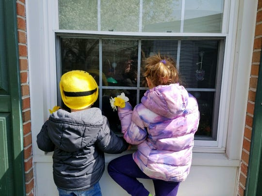 Livie and Collins Marvel visit their great grandmother through a window at the Milford Manor nursing home. Visitors haven't been able to enter nursing homes and assisted-care facilities throughout the state for several days due to the COVID-19 pandemic.