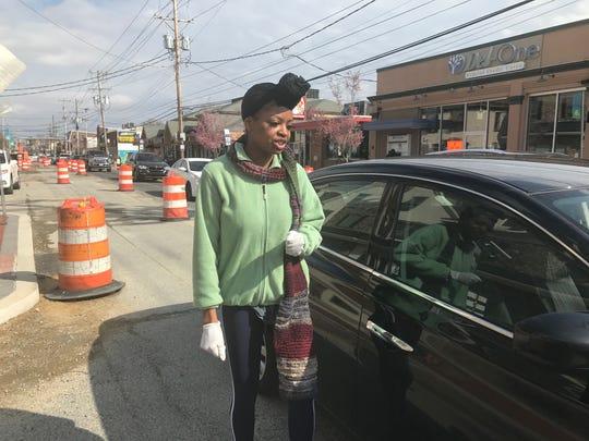 Uber Eats delivery Monique Miller walks back to her car after delivering food on Main Street in Newark.
