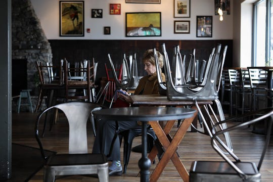 A lone customer sits waiting for a drink at BrewHaHa café, where chairs are stacked on tables after restaurants in Delaware converted to take-out only businesses due to the spread of coronavirus.