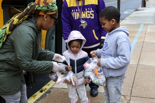 Lavenia Johnson, assistant manager of food services for Red Clay school district, hands meals to Malik (right) and Marvel Massey in front of Warner Elementary on Tuesday. The school is one of the sites where families are able to pick up breakfast and lunch bags during the coronavirus shutdown. The meals are available to anyone age 1 through 18.