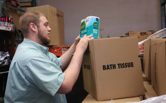 Justin Laube, a grocery worker at Janssen's Market in Greenville, unpacks a fresh shipment of toilet paper to be restocked on Tuesday morning.
