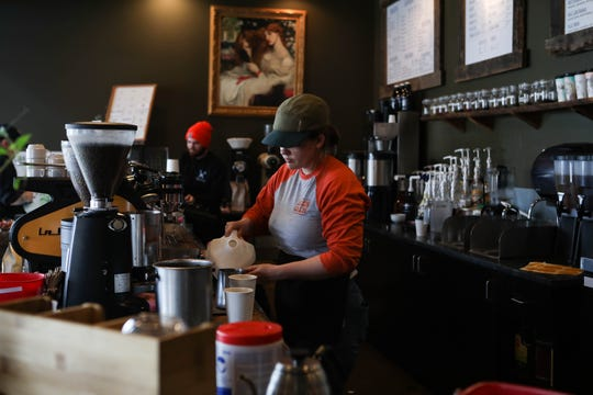"""Barista Caroline Hughes prepares coffee drinks at BrewHaHa café, where chairs sit stacked on tables after restaurants converted to take-out only businesses due to the spread of coronavirus. """"I need to go to work, I need to make money so it's hard to balance it,"""" she said."""