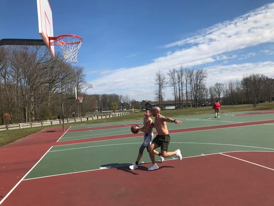 Jayson Herrera, right, and his son, Aiden Herrera, shoot baskets at Glasgow Park Tuesday.
