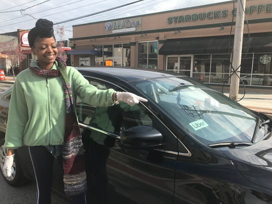 Uber Eats driver Monique Miller points to the Uber sign she uses to let people know who she is making deliveries for.