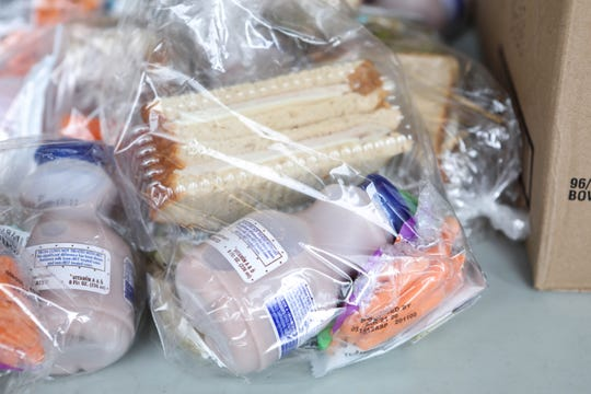 A table holds peanut butter sandwiches, salads and other lunch items in the doorway of Bancroft School on Tuesday. The school is one of the sites where families are able to pick up breakfast and lunch bags each day during the coronavirus shutdown.