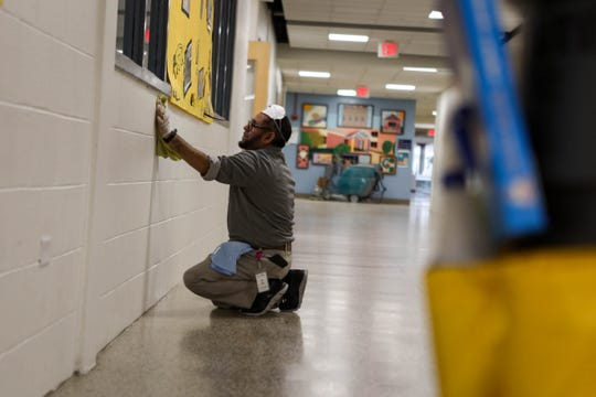 """On a typical Tuesday morning Claymont Elementary would be bustling with kids, but instead a handful of adults don gloves to work in the quiet building. """"First we clean everything,"""" said custodian Abdul Quddus, as he wiped down the wall. """"Then we disinfect."""""""