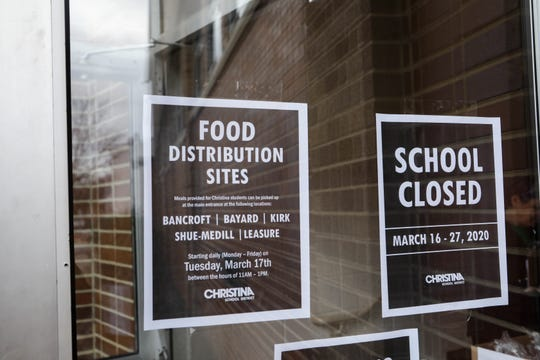 A school closed sign hangs in the doorway of Bancroft School on Tuesday. The school is one of the sites where families are able to pick up breakfast and lunch bags each day during the coronavirus shutdown.