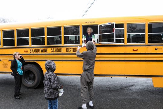 April Ellison hands out meals from a bus window in Claymont. Families are able to pick up breakfast and lunch bags each day during the coronavirus shutdown.