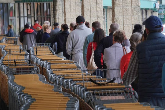 Shoppers file in line as they walk into the Total Wine & More on Naamans Road to buy alcohol on Tuesday morning.