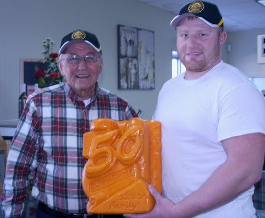 Fred Laack and his grandson, Trevor, are pictured with the 40-pound block of cheese, specially carved to commemorate the 50th anniversary of Dupont Cheese Factory being owned and operated by the Laack family.