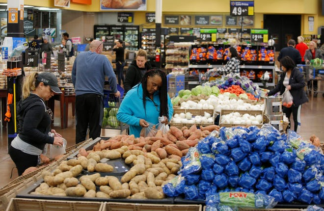 FILE - In this Nov. 27, 2019, file photo people shop for food the day before the Thanksgiving holiday at a Walmart Supercenter in Las Vegas.  U.S. consumer prices increased slightly last month, driven higher by more expensive food. The Labor Department said Wednesday, March 11, 2020, that the consumer price index ticked up 0.1% last month, matching its January increase.