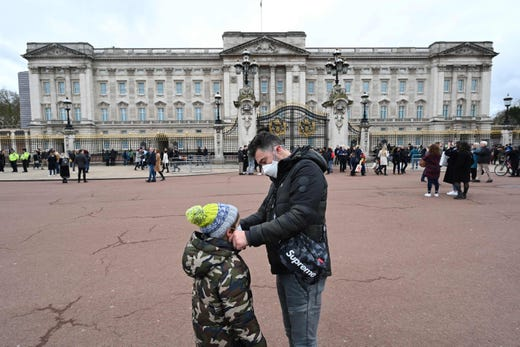 A father adjusts his son's mask between the Queen Victoria Memorial and Buckingham Palace in London on March 14, 2020.