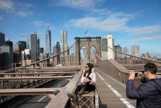 Tourists pose for photos on the Brooklyn Bridge, March 16, 2020 in New York. The bridge's pedestrian and bicycle path is normally crowded on a sunny day.