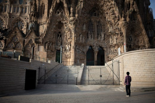 A tourist stands outside the Sagrada Familia basilica in Barcelona, Spain, Friday, March 13, 2020. The basilica closed its doors to visitors and suspended construction on March 13.