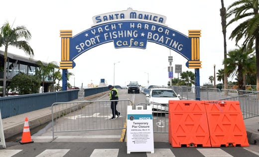 A police vehicle and security guard man the entrance to a closed Santa Monica Pier, one of the most popular tourist attractions in southern California on March 16, 2020 in Santa Monica, Calif.