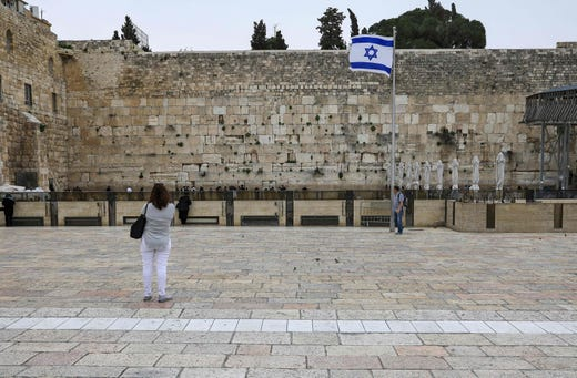 A tourist looks at the nearly deserted Western Wall, Judaism's holiest site, after Israel has imposed some of the world's tightest restrictions to contain COVID-19 coronavirus disease, in Jerusalem on March 12, 2020.