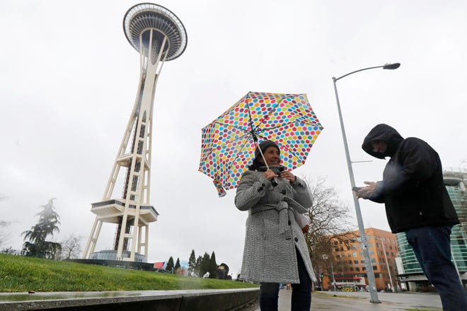Aida Cruz, left, and Jose Chavez, take photos at the Space Needle, March 13, 2020, in Seattle. The two were visiting from San Antonio, Texas and had planned to take the elevator up the Needle for a view of the city, but they discovered that the iconic landmark and tourist attraction had closed Friday and will remain so through the end of March due to the outbreak of the COVID-19 coronavirus in Washington state.