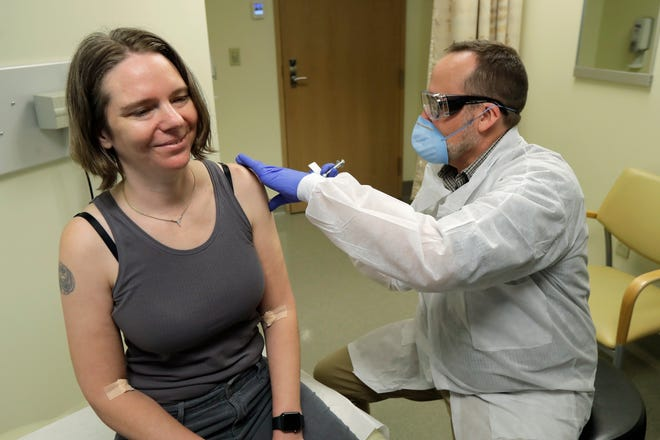 Jennifer Haller, left, smiles as the needle is withdrawn after she was given the first-stage safety study clinical trial of the potential vaccine.