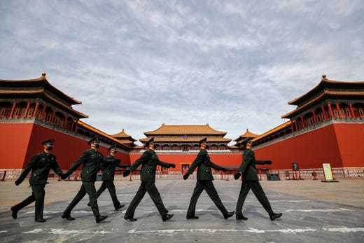 Soldiers wearing protective face masks march past the closed entrance gates to the Forbidden City, usually crowded with tourists before the new coronavirus outbreak in Beijing, March 12, 2020.