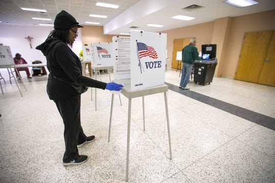 Election judge Marsha Redmond uses gloves and wipes to sanitize each booth after a person votes at St. Bernadette Catholic Church in Rockford, Ill., Tuesday, March 17, 2020.