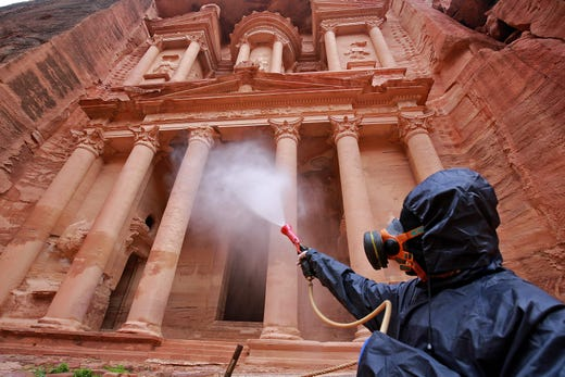 A worker sprays disinfectant in Jordan's archaeological city of Petra south of the capital Amman on March 17, 2020, to prevent the spread of COVID-19.