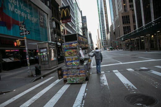 A food truck vendor pushes his cart down an empty street near Times Square in New York, on March 15, 2020.