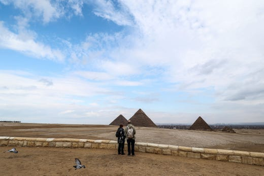 Tourists stand at an overlook by the (L to R) Great Pyramid of Khufu (Cheops), Pyramid of Khafre (Chephren), and Pyramid of Menkaure (Menkheres) at the Giza pyramids necropolis on the southwestern outskirts of the Egyptian capital on March 13, 2020.