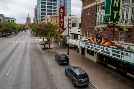 Congress Avenue in Austin, Texas is devoid of its usual heavy traffic in this photo taken around 11:30 a.m. on March 17, 2020, amid the coronavirus outbreak. A hopeful message is on the marquee at the Paramount Theatre.