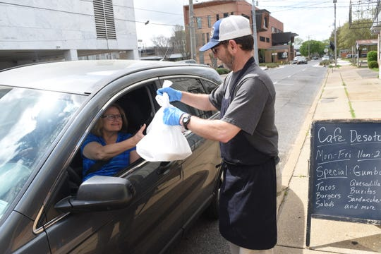 Laura Voltz (left) and Laura Murchinson pick up their to-go orders from Brad Blackwood, owner of Cafe Desoto located on Desoto Street in downtown Alexandria. Blackwood is offering curbside pickup service outside the restaurant or delivery through DoorDash. Local businesses have been trying to adjust to the restrictions due to the Coronavirus.
