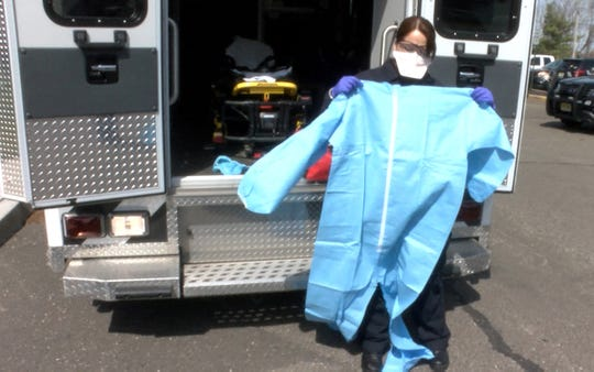Brick Police EMS paramedic Melissa Gaines shows a biohazard suit that is now part of the standard gear, including a mask and saftey glasses, or responding to calls as the coronavirus continues to spread.   She is shown with her ambulance behind police headquarters Wednesday, March 18, 2020.
