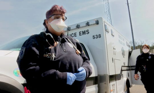 Brick Police EMS EMT Dorothy DePiano (left) and paramedic Melissa Gaines wear the new standard gear - a mask and saftey glasses - for responding to calls as the coronavirus continues to spread.   They are shown with their ambulance behind police headquarters Wednesday, March 18, 2020.