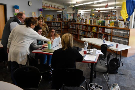 AISD educators work on a core curriculum in science for all AISD second grade students during a meeting Wednesday at the Austin Elementary School library. Teachers and administrators are scrambling to build and implement a ground-up educational plan for homebound students in the new paradigm created by the reaction to the coronavirus.