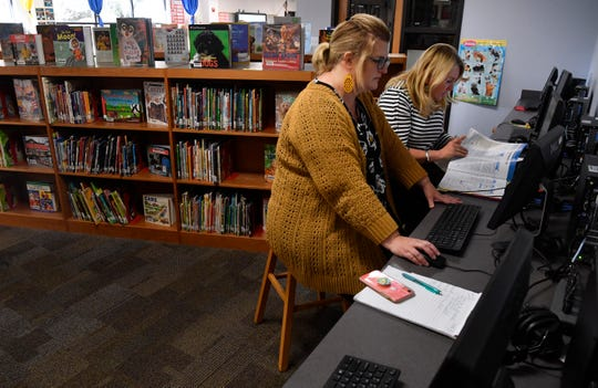 Wendy Morgan navigates a computer at the Austin Elementary School library while Kayla McCoy flips through a reference book Wednesday. Both women teach second grade, Morgan is at Thomas Elementary and McCoy at Johnston. They were adapting an online English Language Arts resource into a core curriculum for students across the Abilene Independent School District.