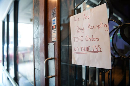 Restaurants on Biltmore Ave, like Hana, had signs on their doors explaining closure or advertising to-go orders March 18, 2020.