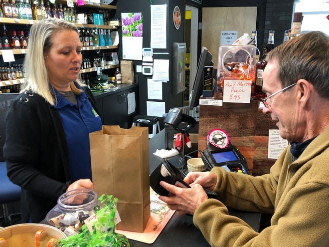 Kelly Brockwell, left, store manager of the Arden ABC store, rings up customer Ronnie Waldrup on Wednesday, March 18. The store, like others in the nine-store Asheville ABC system, has been seeing near-record sales in the wake of the coronavirus pandemic.