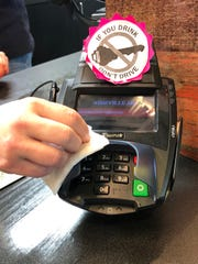 The Arden ABC store, like the other eight in the Asheville ABC system, has employees wiping down credit card machines after every transaction.