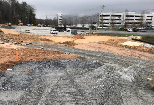 A 300-space shuttle parking lot for Asheville Regional Airport is under construction. The airport's new parking deck is visible across Airport Road.