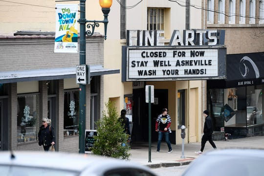 People walk past the Fine Arts Theatre, closed in the midst of COVID-19, in downtown Asheville March 18, 2020.