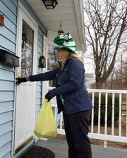 A volunteer from Heineberg Community Senior Center delivers a  pre-packaged meal on March 17, 2020.