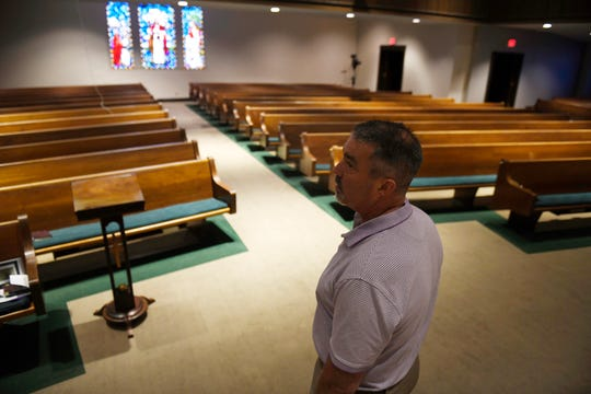 First Baptist Church's Pastor Brian Hill stands in his empty sanctuary, Wednesday, March 18, 2020. Hill and other senior church organizers are following CDC guidelines and limiting groups of more than 50 people.