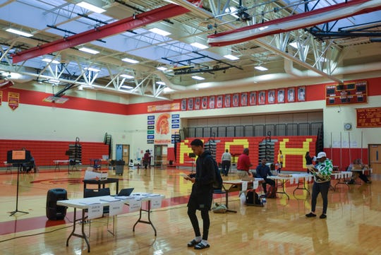 North College Hill Students and parents circle the school's gym, picking up class packets so that they can continue to learn from home during the new coronavirus pandemic.